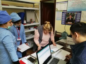 A woman bends over a desk covered with papers. She is surrounded by medical workers in blue scrubs. A man in the Botton right corner works on a laptop.