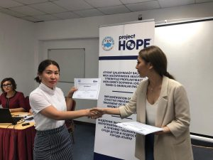 Student receiving certificate at training on TB prevention among children in Kazakhstan